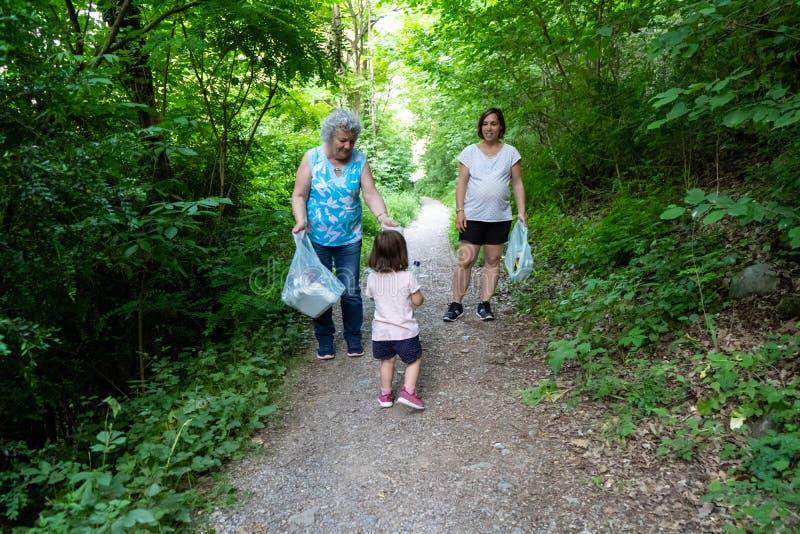 Peu fille, mère enceinte et grand-mère nettoyant la forêt de plastiques photographie stock libre de droits