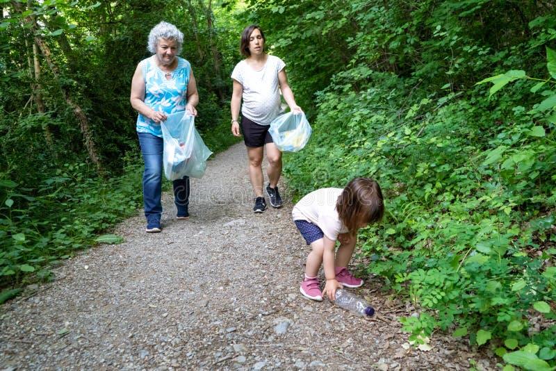 Peu fille, mère enceinte et grand-mère nettoyant la forêt de plastiques images libres de droits