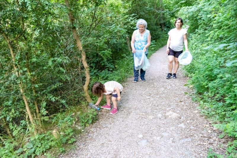Peu fille, mère enceinte et grand-mère nettoyant la forêt de plastiques photos stock