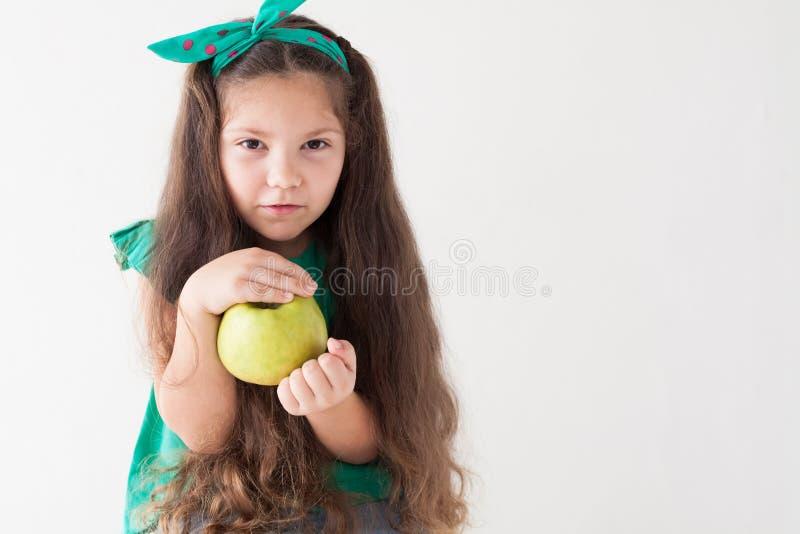 Peu fille mangeant les vitamines vertes d'un fruit d'Apple photographie stock libre de droits