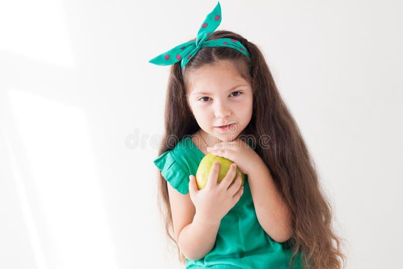 Peu fille mangeant les vitamines vertes d'un fruit d'Apple photo libre de droits