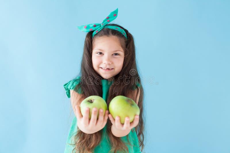 Peu fille mangeant les vitamines vertes d'un fruit d'Apple photographie stock