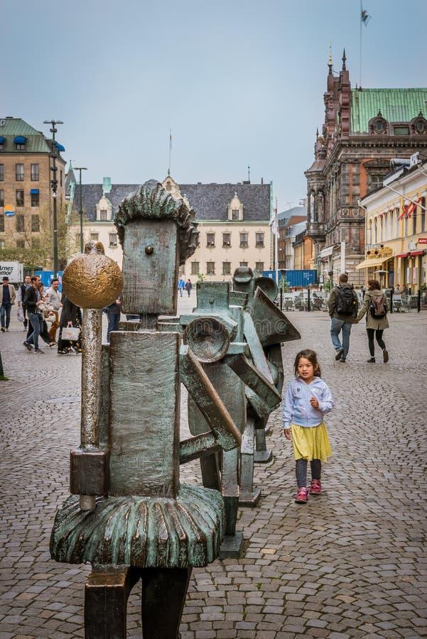 Peu fille marchant le long des statues d'un orchestre de rue à Malmoe, Suède photo stock