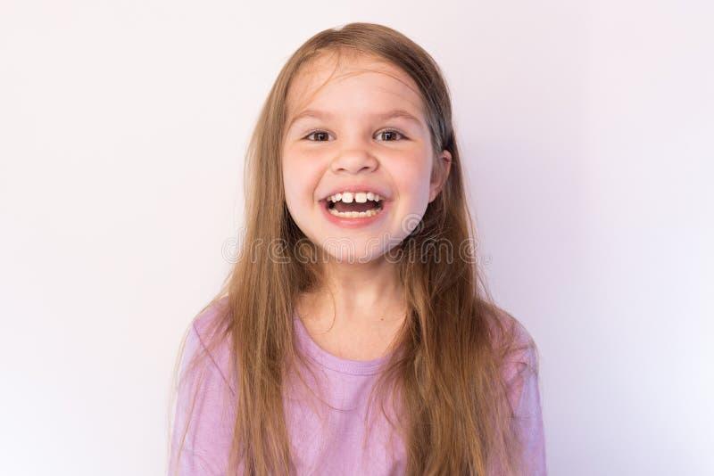 Peu fille mignonne avec une expression satisfaisante sur son visage, souriant largement sur un fond clair image stock
