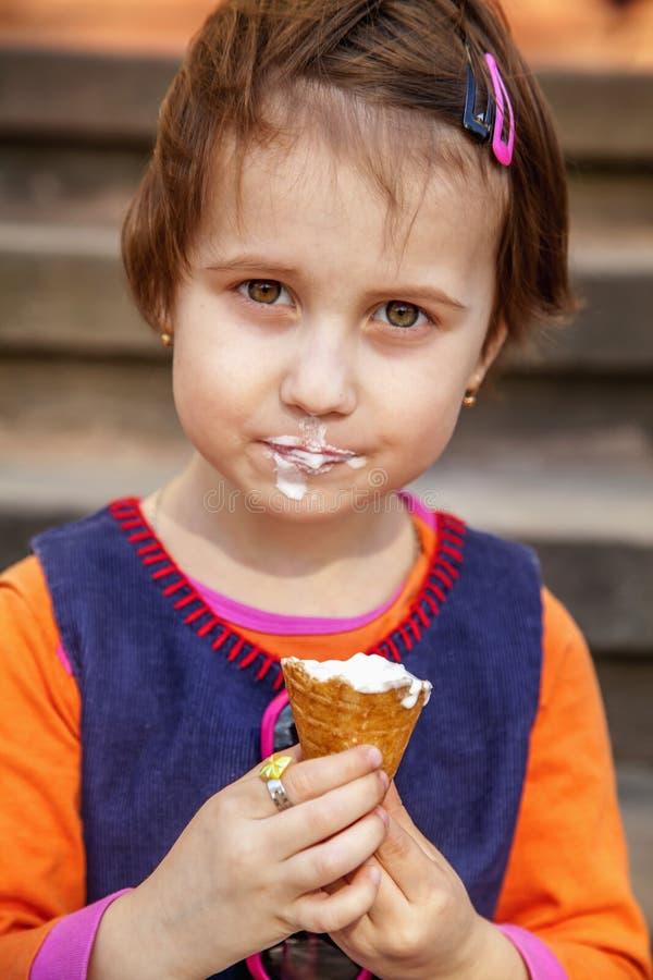 Peu fille mignonne d'enfant mangeant la crème glacée  Nourriture, dessert, enfance heureux, concept d'inattention images libres de droits
