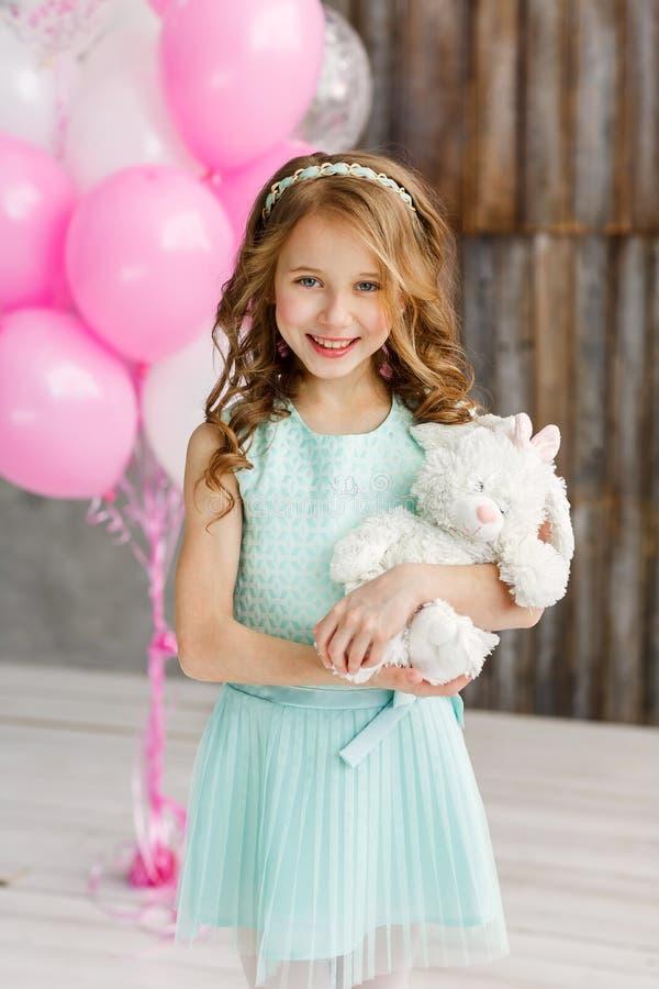 Peu fille mignonne dans le beau styot de robe un studio lumineux et en tenant un jouet mou Concept de joyeux anniversaire images libres de droits