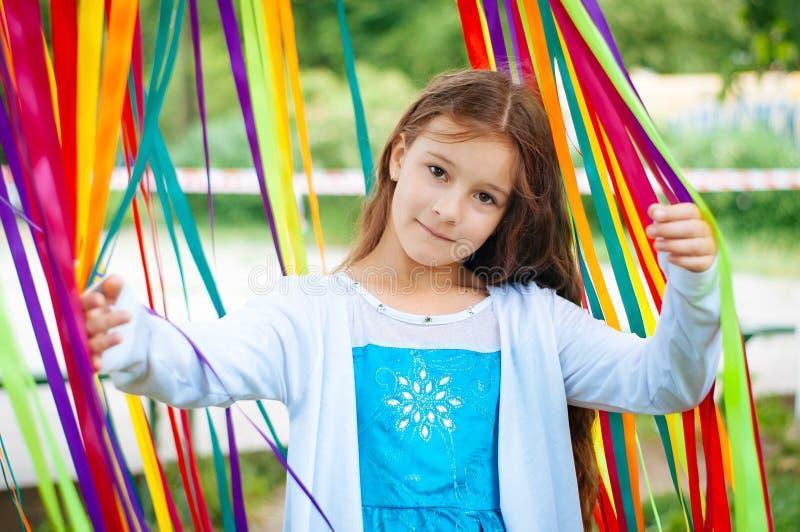 Peu fille mignonne dans une belle robe près de la zone de photo des rubans de fête photos libres de droits