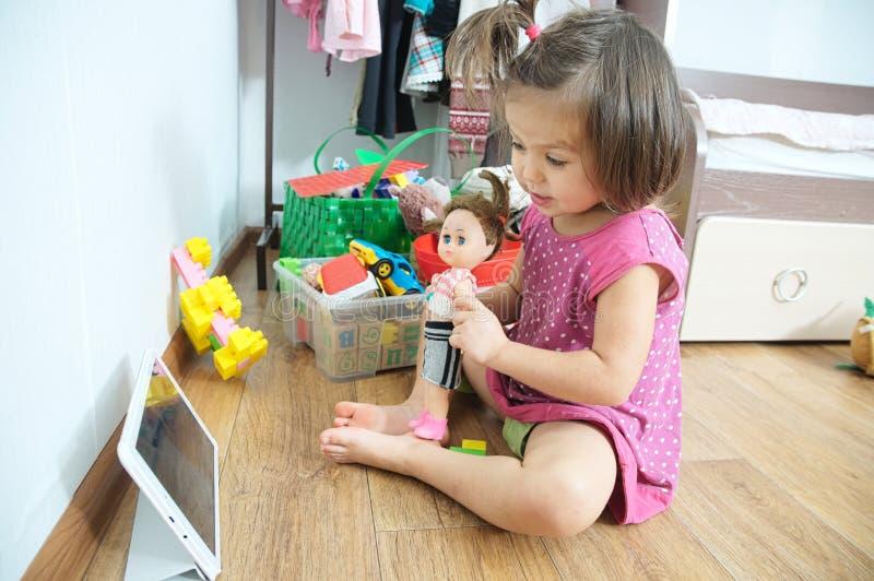 Peu fille montrant sa poupée tout en parlant en ligne par le comprimé avec le grand-père technologie du sans fil dans la vie images libres de droits