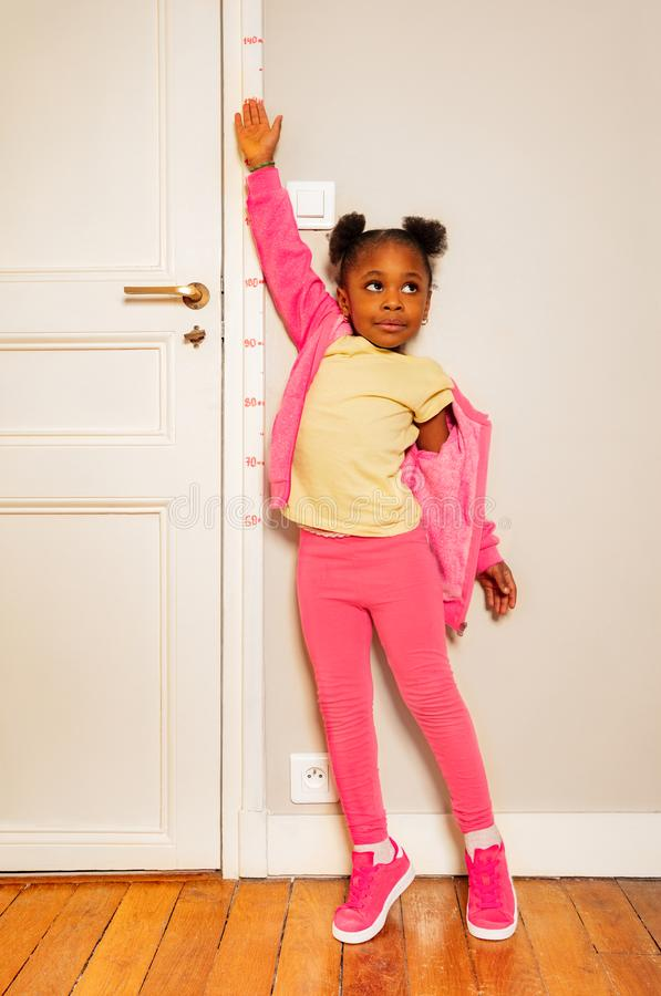 Peu fille noire essayent d'être plus haut sur l'échelle de porte photos libres de droits