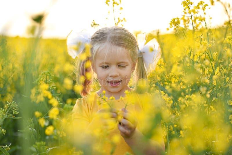 Peu fille riant dans le domaine avec les fleurs jaunes photo libre de droits