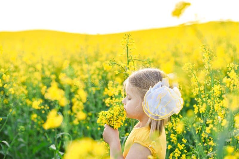 Peu fille romantique dans le domaine avec les fleurs jaunes image stock