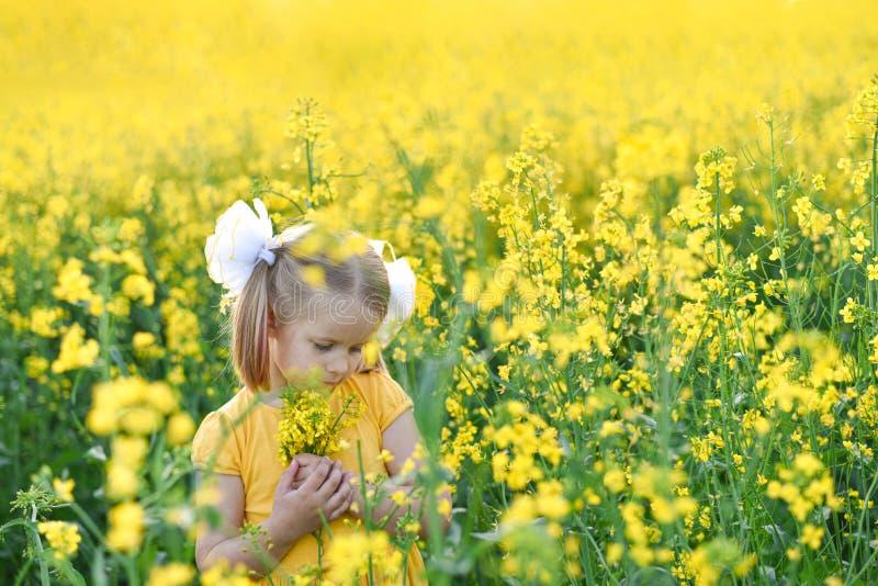 Peu fille romantique dans le domaine avec les fleurs jaunes photo stock
