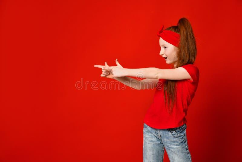Peu fille rousse dans un T-shirt rouge fait un geste avec ses mains aux prises visent image libre de droits