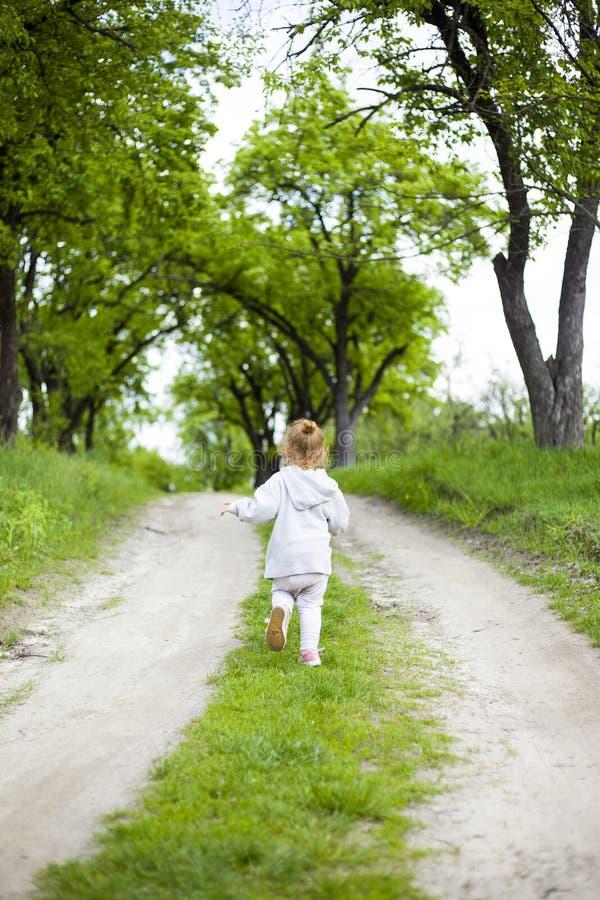Peu fille rousse mignonne fonctionne le long d'un chemin de terre avec l'herbe et les rires photographie stock