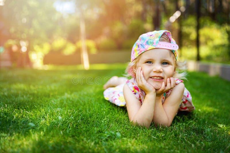 Peu fille s'étendant sur l'herbe verte avec des mains sur l'arrière-cour de joues à la maison images stock