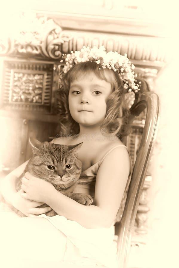 Peu fille s'asseyant avec une guirlande des fleurs sur sa tête avec un grand gros chat photos libres de droits