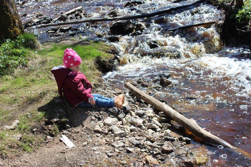 Peu fille s'asseyant près d'une rivière de montagne photo libre de droits