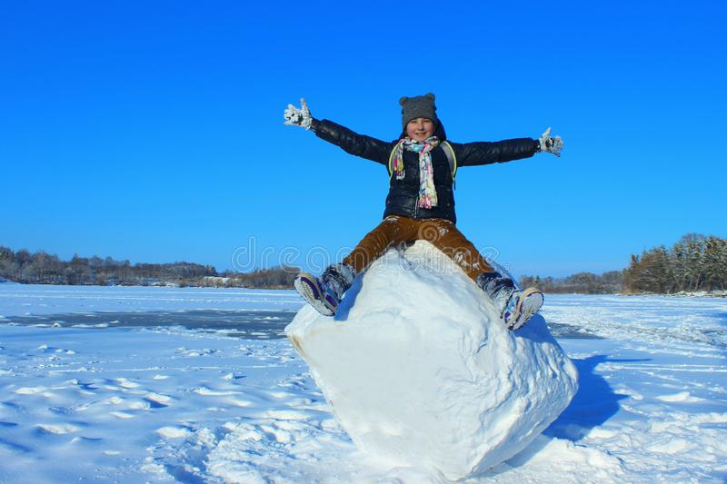 Peu fille s'asseyant sur grand Snowball photo libre de droits