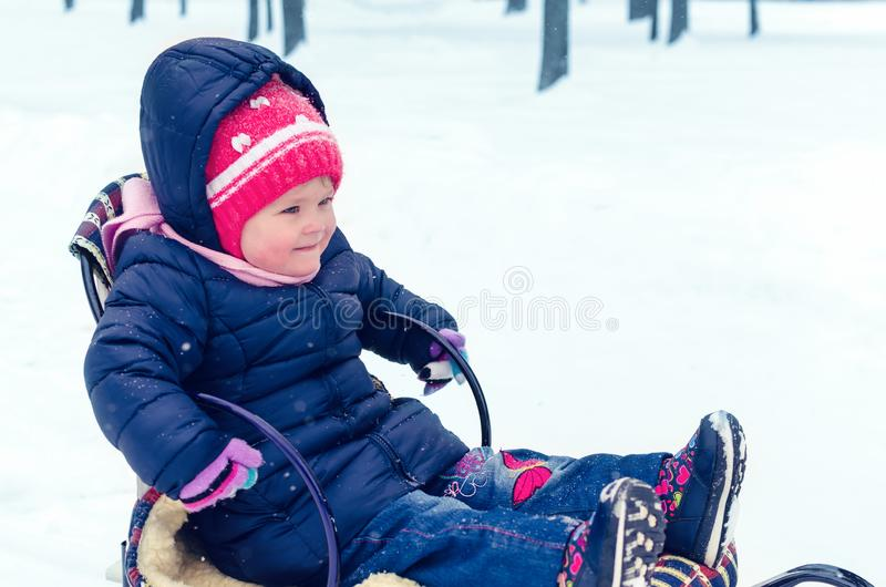 Peu fille s'asseyant sur son traîneau dans le jour d'hiver photos libres de droits