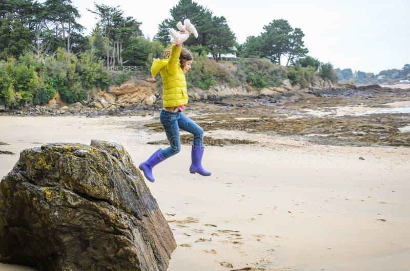 Peu fille sautant de la grande roche sur la plage photo libre de droits
