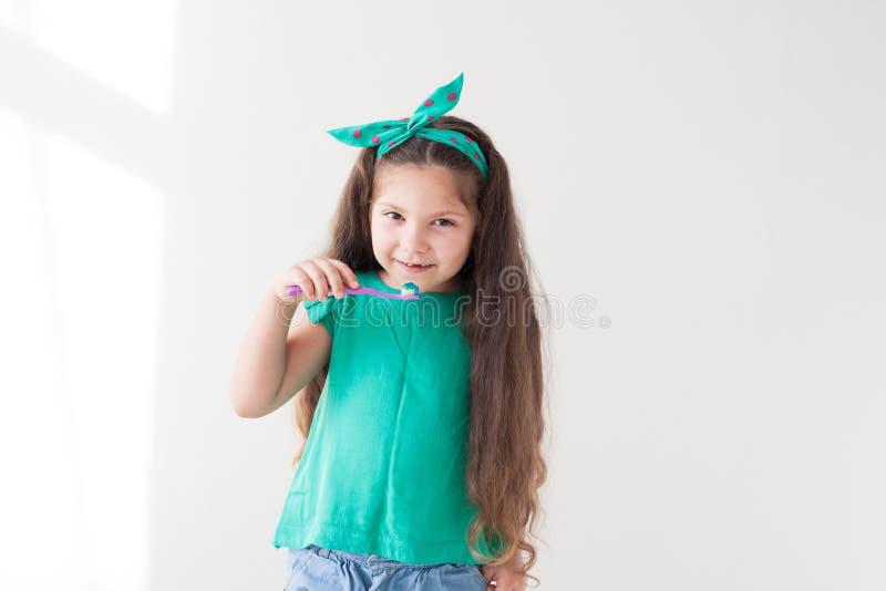 Peu fille se brossant les dents avec une bosselure de brosse à dents images stock