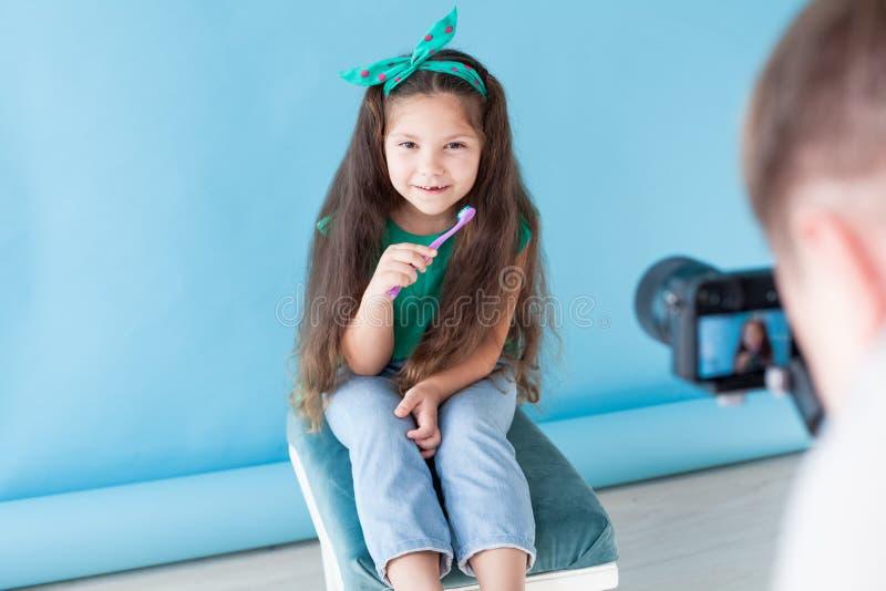 Peu fille se brossant les dents avec une bosselure de brosse à dents photographie stock