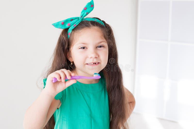 Peu fille se brossant les dents avec une bosselure de brosse à dents photos libres de droits