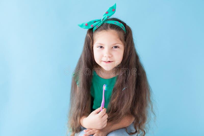 Peu fille se brossant les dents avec une bosselure de brosse à dents photo stock