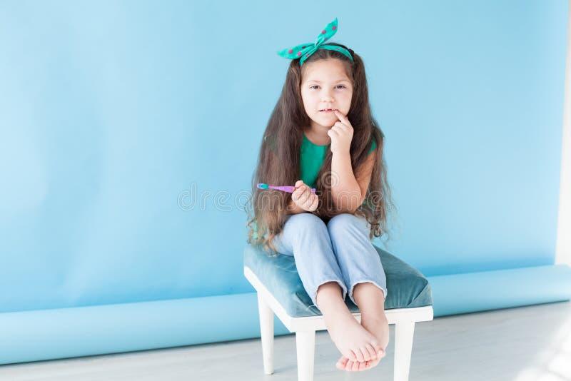 Peu fille se brossant les dents avec une dent d'art dentaire de brosse à dents photographie stock libre de droits