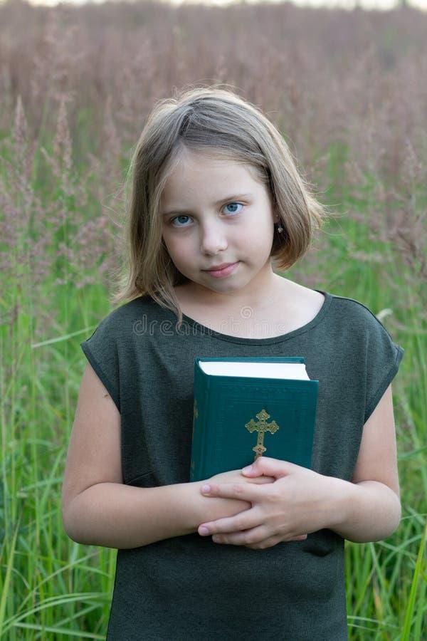 Peu fille se tient avec la bible photo libre de droits