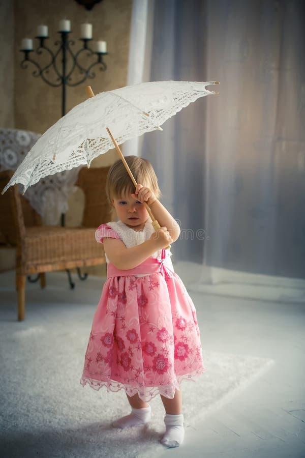 Peu fille tenant un parapluie pour le soleil photographie stock libre de droits