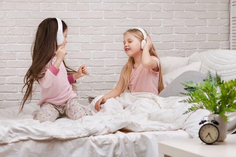 Peu filles d'enfants écoutant la musique avec les écouteurs photographie stock libre de droits