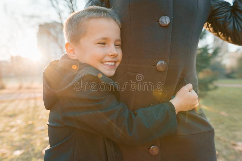Peu fils étreignant sa mère, garçon souriant, jour ensoleillé en parc, heure d'or images stock