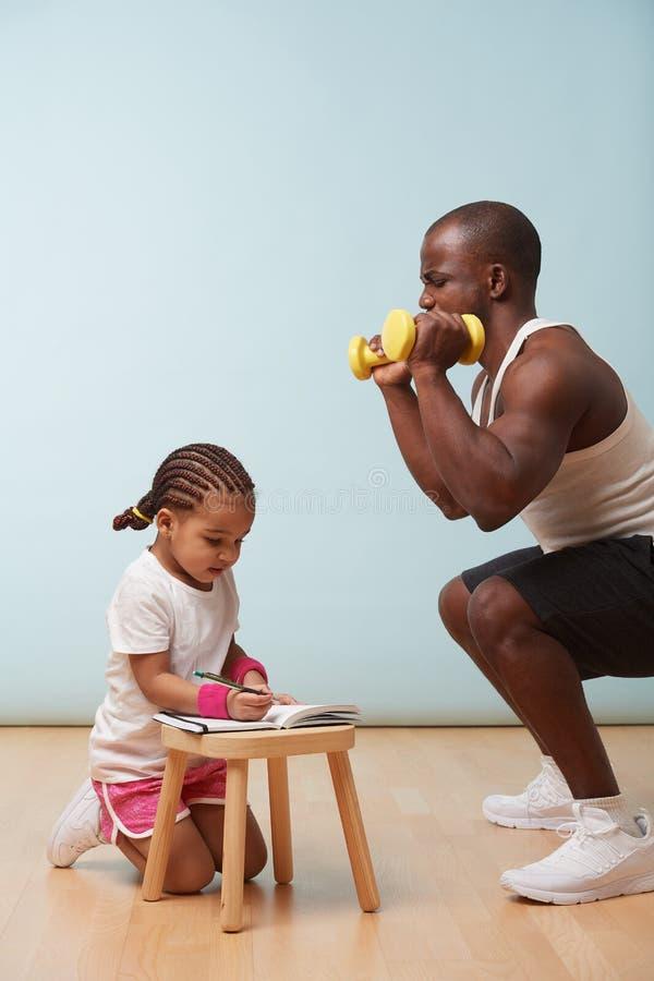 Peu forme physique de fille formant son père Effectuer des notes Jeu de rôle d'enfant image stock