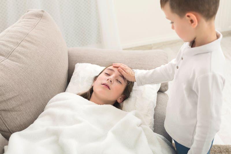 Peu frère touchant le front de la soeur à la maison photo stock