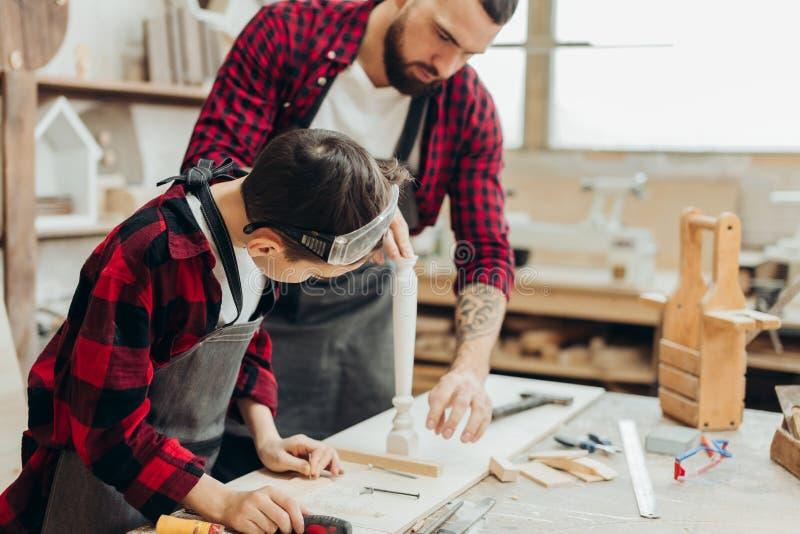 Peu garçon aide son père de charpentier mesurant la planche en bois dans l'atelier photos libres de droits