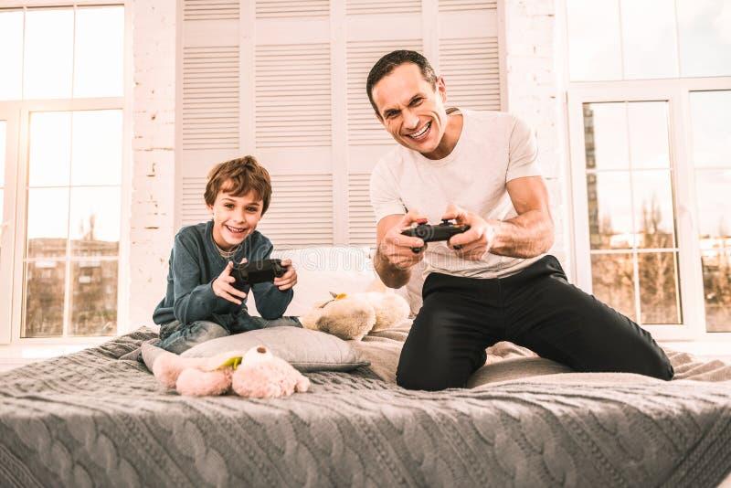 Peu garçon appréciant une soirée folle jouant des jeux avec son papa photos stock