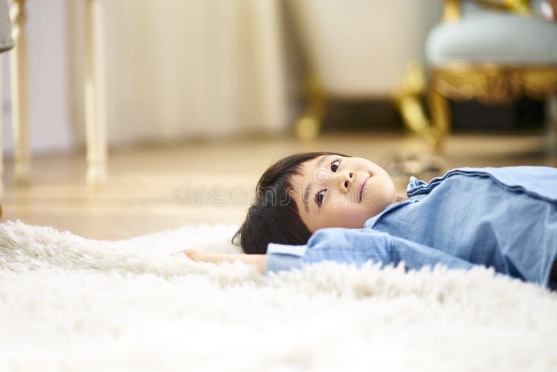 Peu garçon asiatique se trouvant sur le dos sur le tapis photographie stock