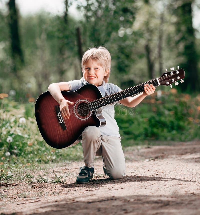 Peu garçon avec la guitare sur le boulevard en parc photographie stock