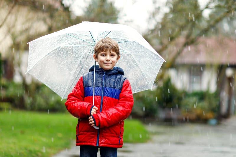 Peu garçon blond d'enfant sur le chemin à l'école marchant pendant le verglas, la pluie et la neige avec un parapluie le jour fro photographie stock libre de droits