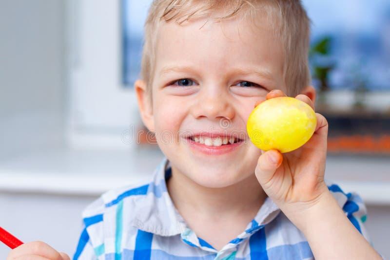 Peu garçon blond se prépare à Pâques et aux oeufs de peinture Repères colorés Concept de Pâques et de vacances images stock