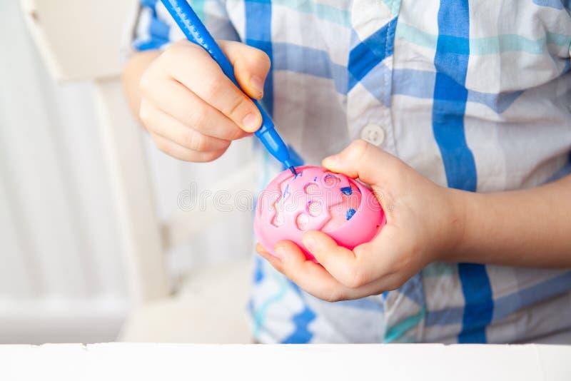 Peu garçon blond se prépare à Pâques et aux oeufs de peinture Repères colorés Concept de Pâques et de vacances photo libre de droits