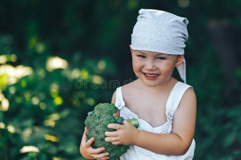 Peu garçon de sourire heureux d'agriculteur dans les combinaisons blanches et le bandeau gris tenant le brocoli organique frais d photo libre de droits