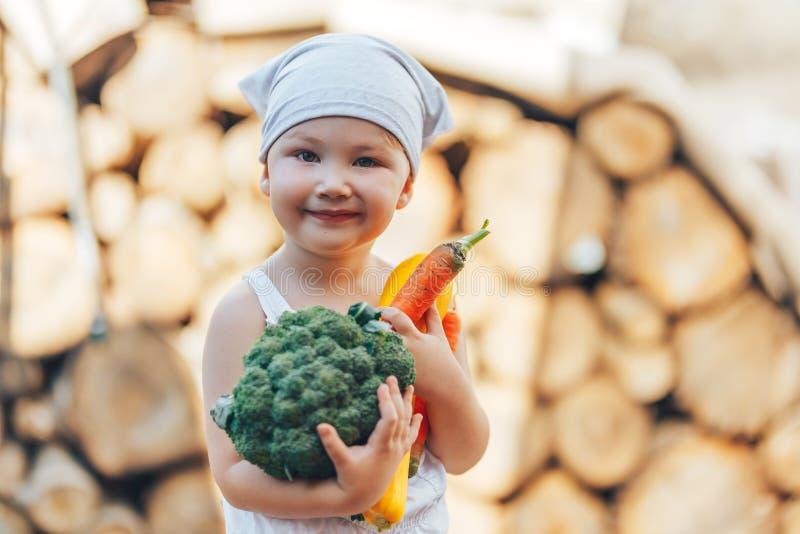 Peu garçon de sourire heureux d'agriculteur dans les combinaisons blanches et le bandeau gris tenant les légumes organiques frais image stock