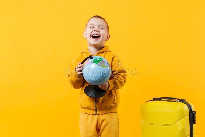 Peu garçon de touristes d'enfant de voyageur 3-4 années d'isolement sur le studio jaune-orange de fond de mur Déplacement de pass image stock