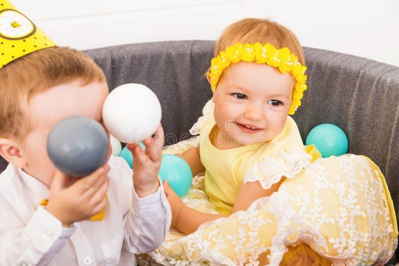 Peu garçon et fille célèbrent l'anniversaire dans une piscine avec les boules en plastique photo stock
