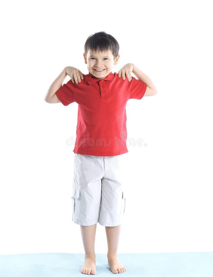Peu garçon exécute des exercices de matin D'isolement sur le blanc Photo avec l'espace de copie image stock