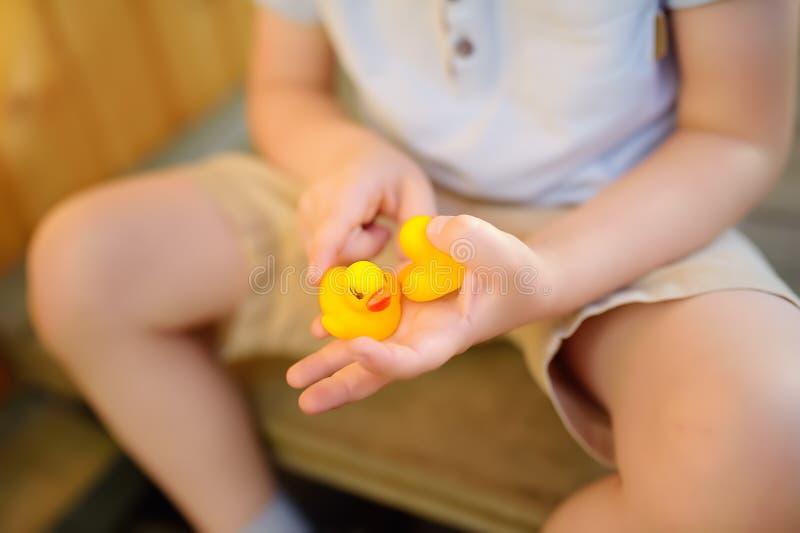 Peu garçon jouant avec la famille du canard en caoutchouc photo stock
