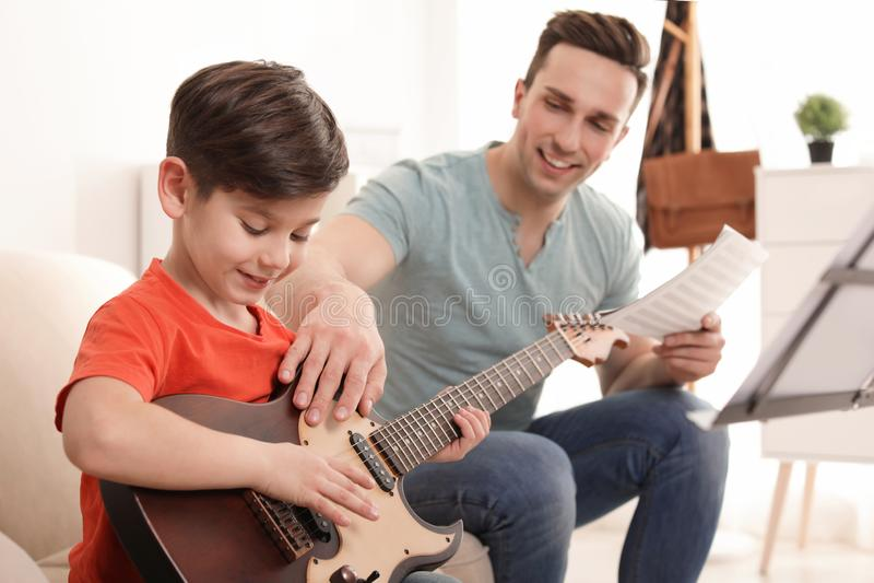 Peu garçon jouant la guitare avec son professeur à la leçon de musique photos stock