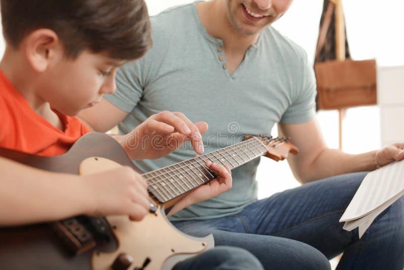 Peu garçon jouant la guitare avec son professeur à la leçon de musique Apprentissage des notes photos libres de droits